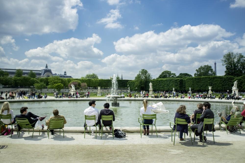 Leute sitzen im Mai 2013 während der Mittagspause im Jardin des Tuileries in Paris an einem Wasserspiel